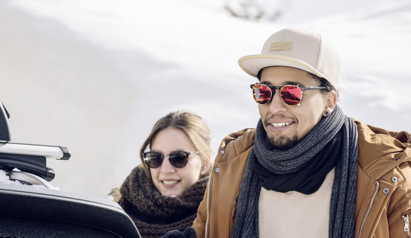 Smiling couple in winter jackets beside snow-covered car